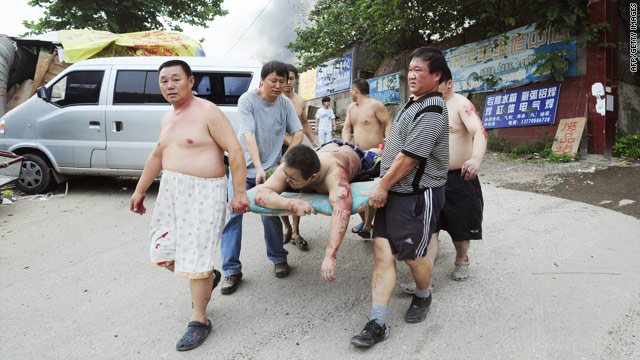People carry a man wounded in an explosion at a plastic factory in Nanjing, east China's Jiangsu province on July 28, 2010.
