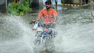 A Pakistani motorcyclist rides through a flooded street during heavy monsoon rains in Karachi.