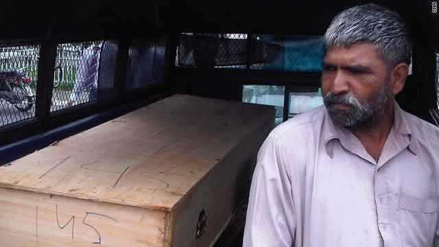 A volunteer sits next to a coffin at a makeshift morgue at Islamabad, Pakistan's main hospital.