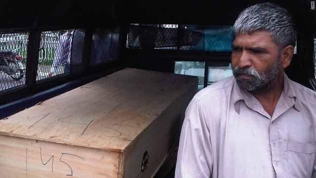 A volunteer sits next to a coffin at a makeshift morgue at Islamabad, Pakistan's main hospital.