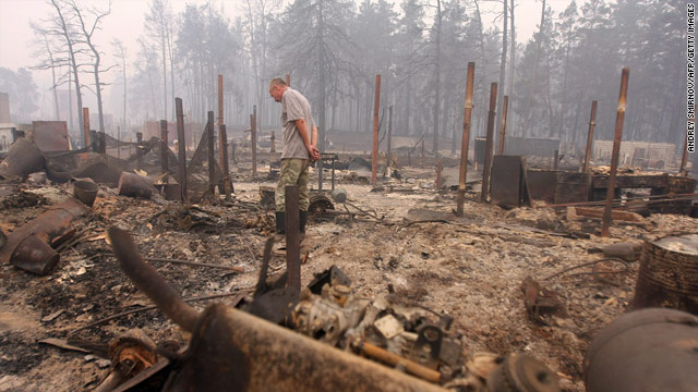A man inspects the ruins of his house in the village of Beloomut, Russia, after wildfires ravaged the area.