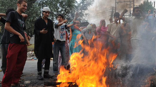 Protesters defy a curfew as they gather to set a fire alight during a demonstration in Srinagar.