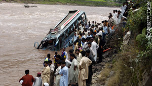 Onlookers stand over the site of a deadly bus crash in Pakistan on Thursday.