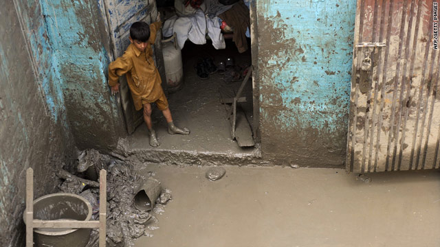 A Pakistani boy stands in his house after flash floods in Nowshera on August 5, 2010.