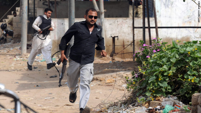 A plain-clothed Pakistani policeman retreats from gunfire in the eastern neighborhood of Karachi on August 4, 2010.