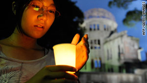 A Japanese girl prays for victims of the atomic bombing at Peace Memorial Park in Hiroshima on Thursday.