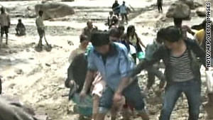 Television picture from NDTV shows residents in Leh struggling with the floodwater on August 6, 2010.