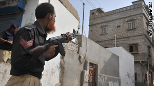 A policeman stands guard in a troubled eastern neighbourhood of Karachi on August 4, 2010.