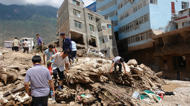 Residents make their way along a street in Zhouqu in northwest China's Gansu province Sunday after a deadly flood-triggered landslide.