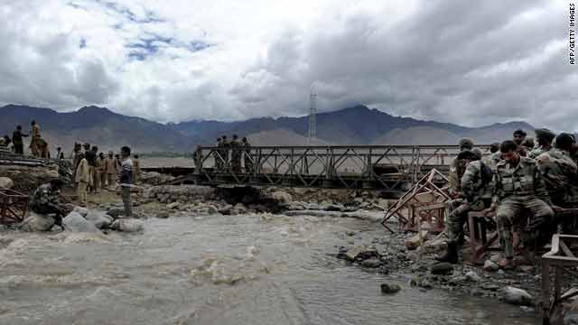 Indian army personnel rest after setting up a temporary bridge at Choglamsar village in Leh on Sunday.