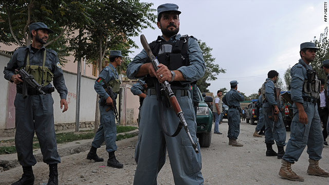 Afghan police stand guard near the scene of a suicide bomb attack at a guest house in Kabul on August 10, 2010.