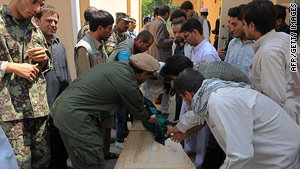 Friends and family attend to the coffin of a slain Afghan aid worker this week at a Kabul, Afghanistan, morgue.
