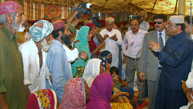Pakistan president Asif Ali Zardari talks to flood survivors during a visit to a relief camp in Sukkur on August 12, 2010.