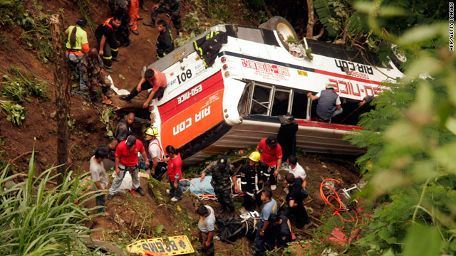Rescuers remove bodies from the wreckage of a bus that plunged into a deep ravine in the Philippines on August 18, 2010.
