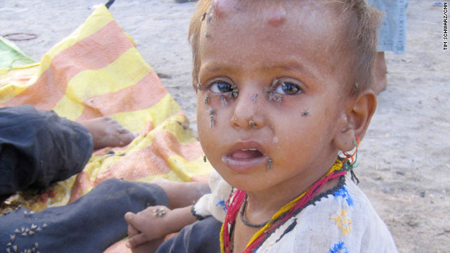 Flies cover a child at a school turned into a camp for flood victims in Sukkur, Pakistan.