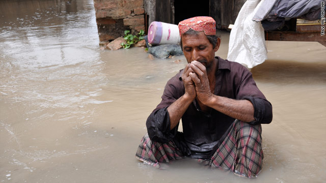 Ghous Chacher sits outside his flooded home Tuesday in Karampur, Pakistan. Thousands of people are cut off from help.