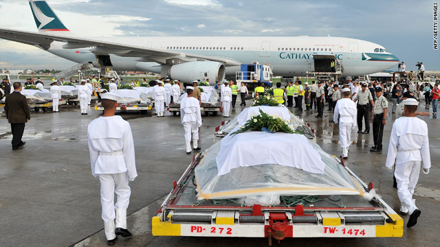 Coffins of victims are loaded onto a plane at Manila on Wednesday to be flown home to Hong Kong.