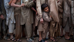 Flood survivors wait in line to recieve water relief supplies in Pabi, Pakistan.