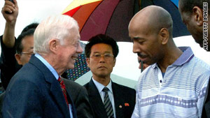 Former U.S. President Jimmy Carter shakes hands with Aijalon Mahli Gomes before they leave Pyongyang.
