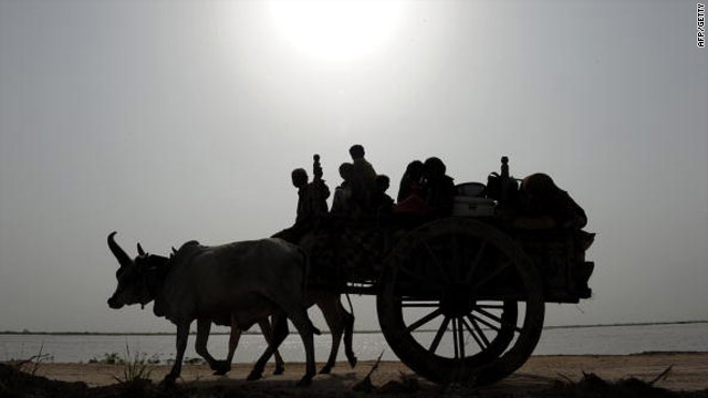 Flood-hit villagers ride and their belongings on a bullock cart on the outskirts of Sajawal, Sindh province, Pakistan on August 25