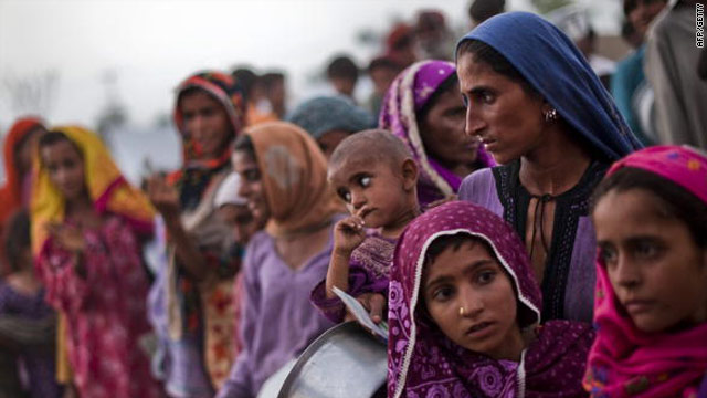 Pakistani villagers made homeless by the floods line up for food August 27 at a relief camp line in Sukkar.