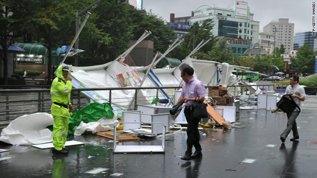 People walk past booths damaged by Typhoon Kompasu in Seoul, South Korea, on Thursday.