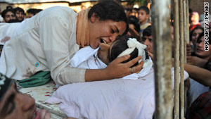 A woman holds the body of a relative at his home north of Srinagar on September 6, 2010.