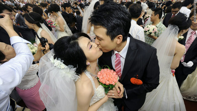 A newly wed couple kiss during a mass wedding ceremony organized by Taipei city government on September 9, 2010.