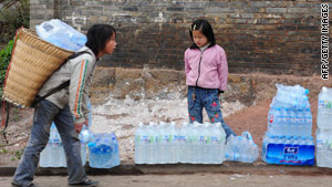Children carry bottled drinking water home in Yunnan province earlier this year.