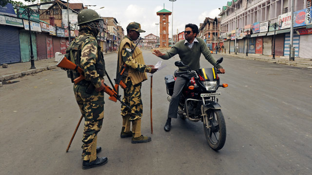 Indian security personnel check a Kashmiri man's curfew pass in the summer capital Srinagar on September 15, 2010.