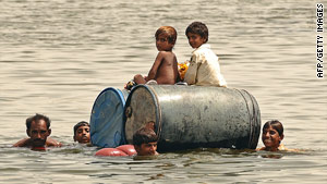 Children cross a flooded area on empty oil drums in Pakistan's Sindh Province on Thursday.