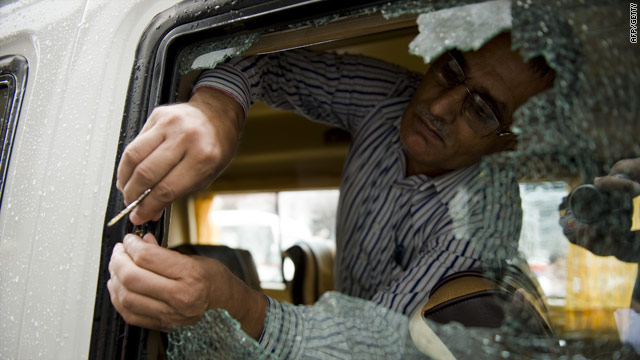 A policeman retrieves a bullet lodged in a window in New Delhi on Sunday after gunmen opened fire on the tourist bus.