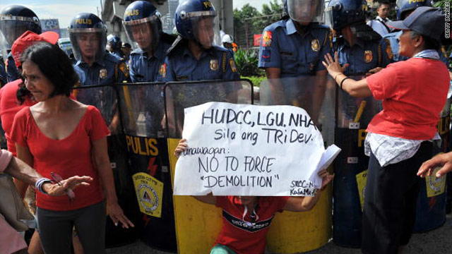 A local resident protests in front of policemen during the demolition of shanty homes in Manila on September 23.