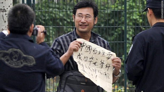 "A protestor shows his banner declaring ""Chinese people demand Japan to release unconditionally the Chinese captain"" as police film him in front of the Japanese embassy in Beijing on September 20, 2010."