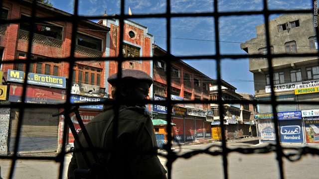 An Indian paramilitary trooper stands guard on a curfew bound street in Srinagar on September 24.