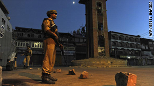 An Indian paramilitary soldier stands guard in a curfew bound street in Srinagar.