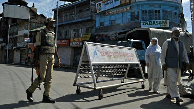 Kashmiri people walk past an Indian paramilitary trooper on patrol during a curfew Friday in Srinagar, India.