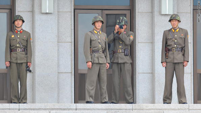 A North Korean soldier takes picture of the southern side of the cross-border village of Panmunjeom on July 27.