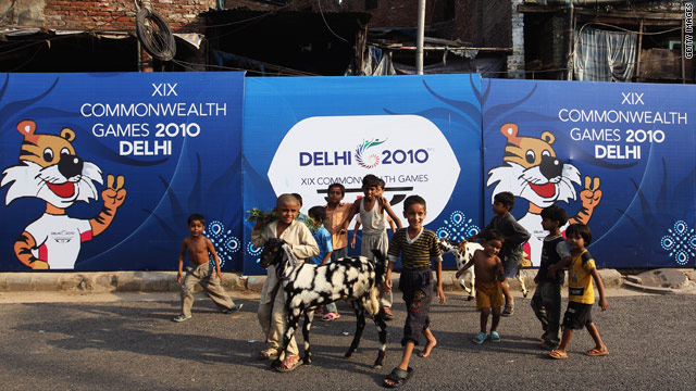 Children walk past signs in New Delhi, India, on Saturday promoting the 2010 Commonwealth Games, which begin on Sunday.