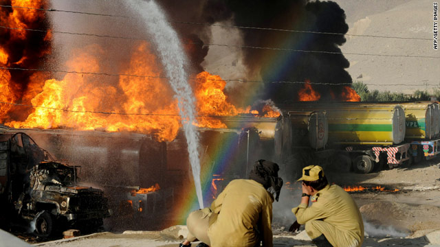 Pakistani firefighters try to extinguish burning NATO oil tankers following a gunmen attack in Quetta on October 6, 2010.