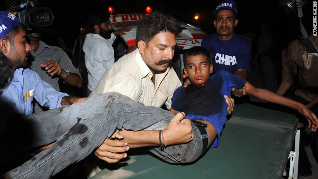 Pakistani volunteers shift an injured blast victim to a hospital in Karachi.