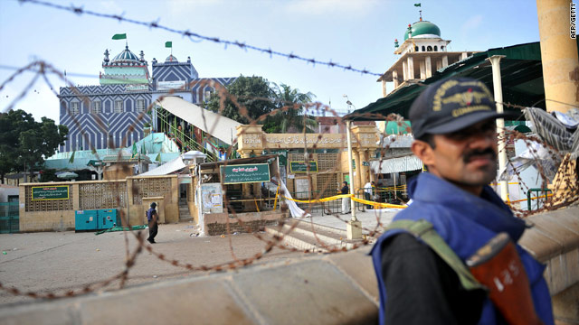 Police commandos guard the Sufi shrine in Karachi on Friday a day after twin suicide bomb blasts killed at least nine.
