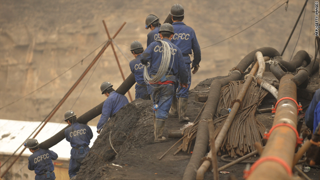 Mine workers carry pipes to the entrance to the Wangjialing coal mine during rescue efforts on March 31.