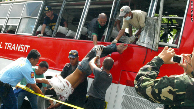 Police remove a passenger from a bus after an explosion on the Philippines southern island of Mindanao on October 21, 2010.