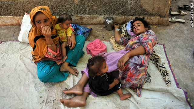 Jannat Khatoon, right, lies outside a Hyderabad, Pakistan, hospital while a relative takes care of Khatoon's ill children.