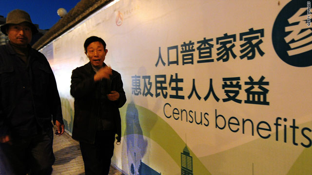 Pedestrians walk past a billboard for China's census on October 29, 2010, in Beijing, China.