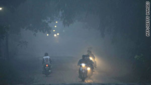 The air is thick with volcanic ash as residents flee on motorcycle in Klaten district, central Java.