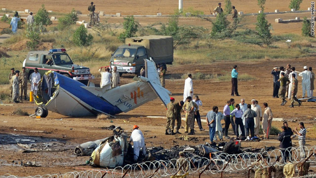 Pakistani rescuers and airport security personnel gather at an aircraft crash site in Karachi on November 5, 2010.
