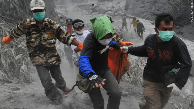 Rescue teams rush through the the dry, hot mud Sunday to evacuate victims of the volcano.