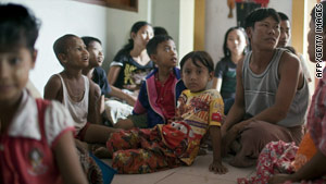 Refugees who fled fighting in Myanmar wait in a shelter set up by the Thai government on Monday.